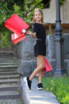 色付きのバッグと公園を歩く美しい少女