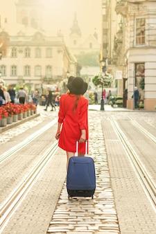 Красивая маленькая девочка, идущая с голубым чемоданом.