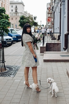 Beautiful young girl walking with little pet white dog on city street outdoor domestic animals femal...