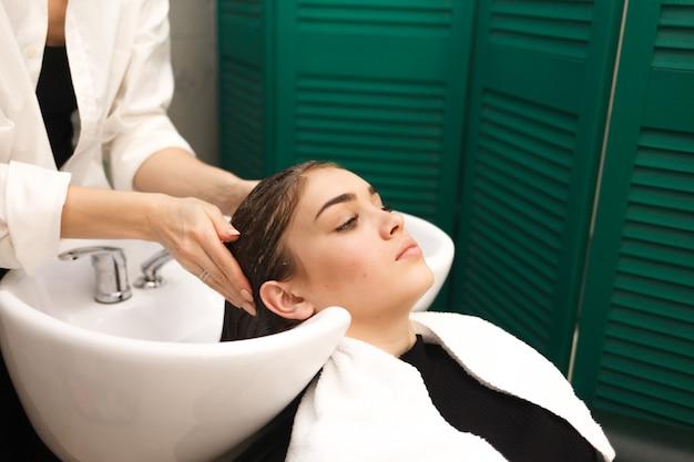 美しい少女は、美しさで頭を洗います。美容師はクライアントの髪を洗っています