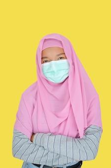 美しい少女は黄色の背景にピンクのヒジャーブとマスクを着用します