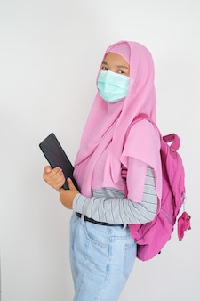 Beautiful young girl wear pink hijab and mask hold laptop on white background