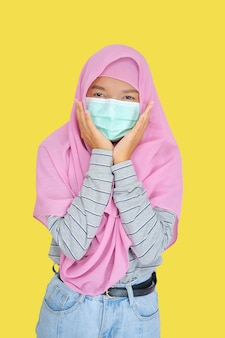 Beautiful young girl wear pink hijab and mask on yellow background