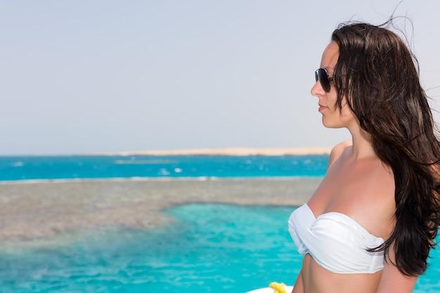 晴れた夏の日にボートで白い水着とサングラスを身に着けている美しい少女