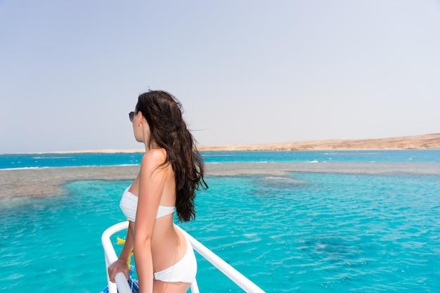 晴れた夏の日に美しいターコイズブルーの海を見ているボートに白い水着とサングラスを身に着けている美しい少女