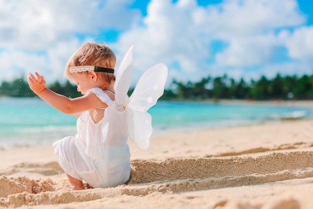 Beautiful young girl wearing angel wings on the beach