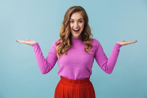 Красивая молодая девушка в повседневной одежде, стоящая изолированно над синей стеной, представляя копию пространства