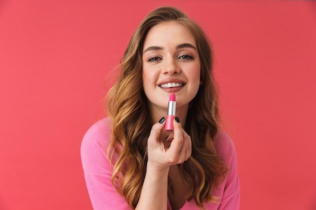 캐주얼 옷을 입은 아름다운 어린 소녀가 분홍색 벽에 고립되어 립스틱으로 화장을 하고 있다