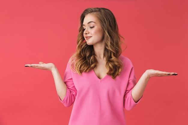 Красивая молодая девушка в повседневной одежде, стоящая изолированно над розовой стеной, представляя копию пространства