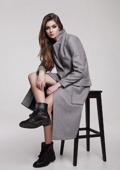 Красивая молодая девушка в длинном сером пиджаке