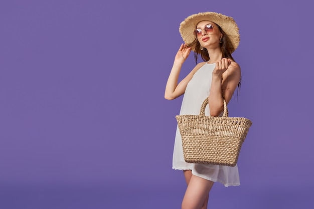 スタジオでポーズをとる麦わら帽子と素敵な動物柄のドレスを着ている美しい少女