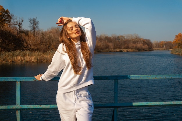 Beautiful young girl in white clothes stands on the bridge