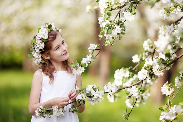 Beautiful young girl in white dress in the garden with blosoming  apple trees. cute girl  holding apple-tree branch