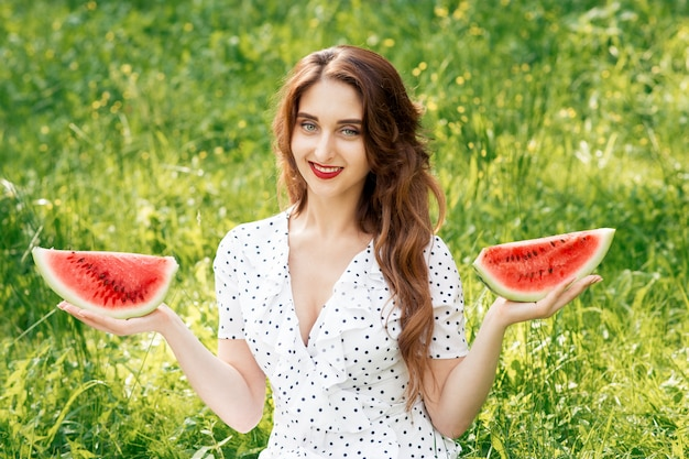 Beautiful young girl in white holds two pieces of fresh watermelon.