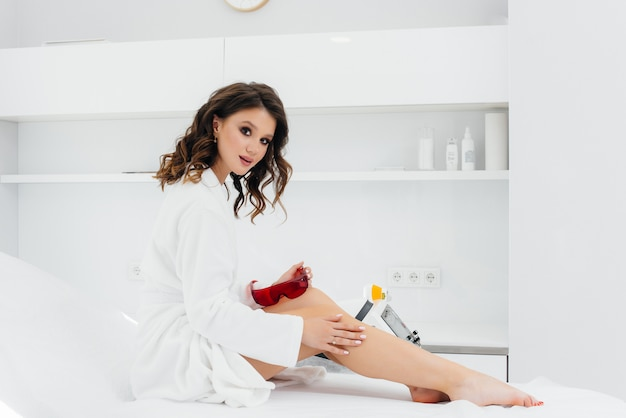 A beautiful young girl will undergo laser hair removal with modern equipment in a spa salon. beauty salon. body care.