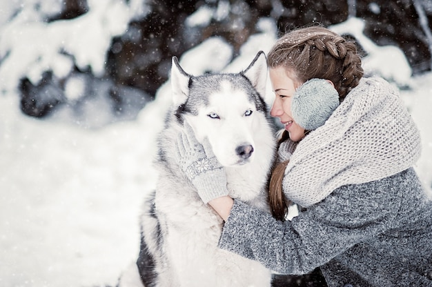 Beautiful young girl in winter forest with siberian husky. symbol of new year 2018