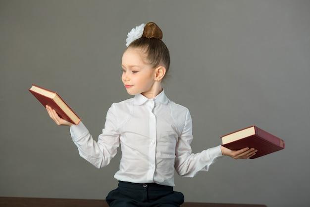 手に本を持ってテーブルに座っている弓を持つ美しい少女
