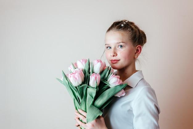 春の花の束、女性の日、母の日のグリーティングカードを持つ美しい少女