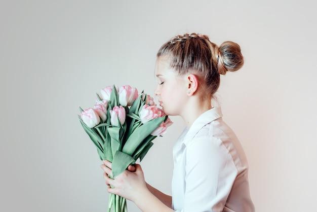 春の花、女性の日、母の日のグリーティングカードの束を持つ美しい少女
