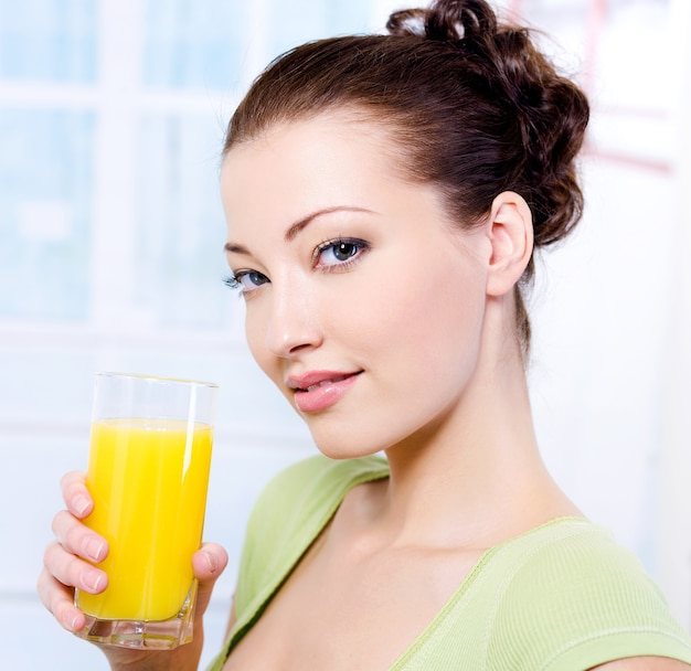 新鮮なオレンジジュースのガラスを持つ美しい少女