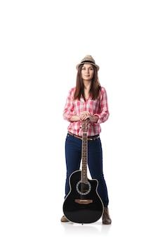 Красивая молодая девушка с гитарой в рубашке и шляпе стоит на белом фоне.
