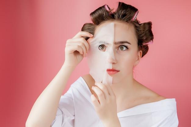 마스크와 curlers 그녀의 얼굴을 만지고 아름 다운 어린 소녀