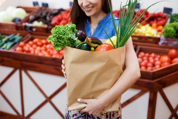 야채가 게에서 쇼핑 종이 봉투와 함께 아름 다운 소녀
