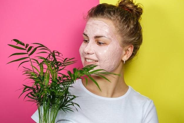 彼女の顔にさわやかなマスクを持つ美しい少女。装飾的な手のひらを手に持っています。美しさと健康な肌