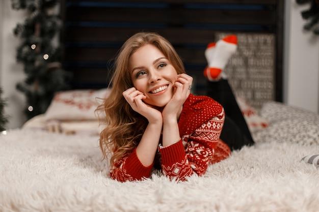 赤い流行のセーターで笑顔の美しい少女はベッドに横たわって夢を見る