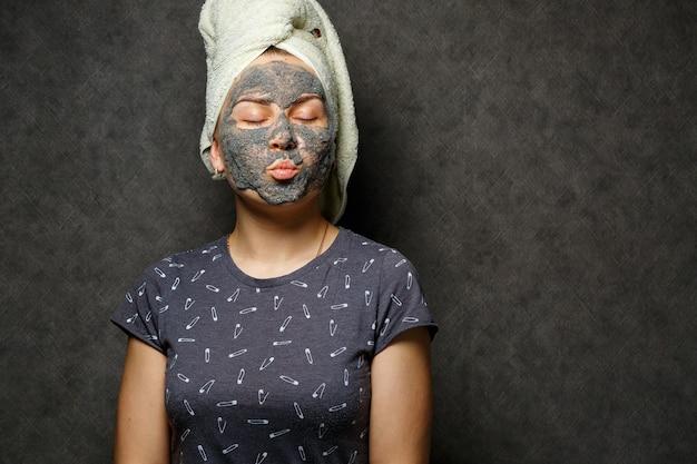 얼굴에 강장제 폼 마스크를 쓰고 수건을 머리에 묶은 아름다운 소녀