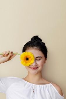 黄色いガーベラの花を持つ美しい少女