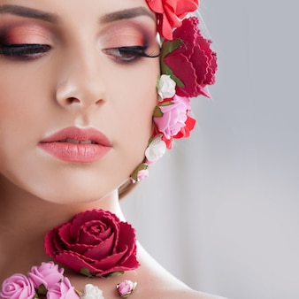 Beautiful young girl with applique flowers on the face.