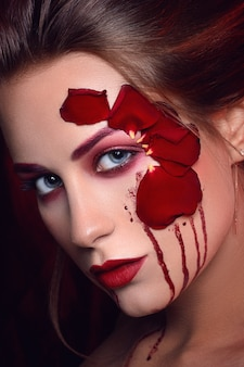 Beautiful young girl with applique red roses flowers on the face