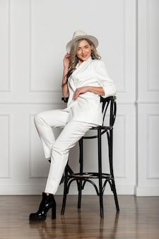 Beautiful young girl with a beautiful figure in a white trouser suit and a wide-brimmed white hat posing against a white background in the studio. sitting on a chair