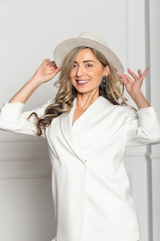 Beautiful young girl with a beautiful figure in a white trouser suit and a wide-brimmed white hat posing against a white background in the studio. woman smiling