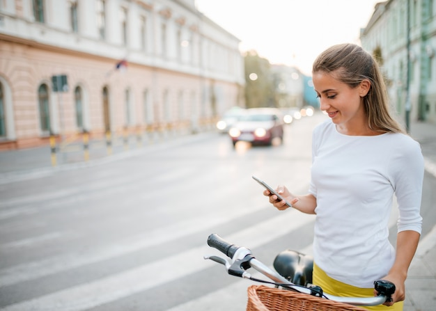 Beautiful young girl with a bike using a phone in the city.