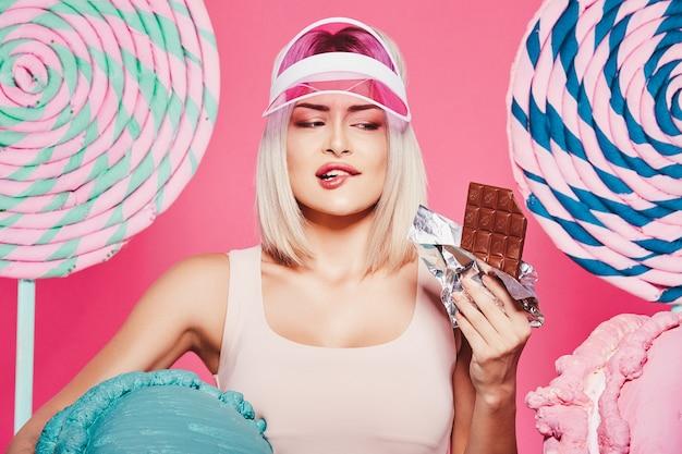 분홍색에서 거대한 달콤한 막대 사탕으로 서있는 상단과 치마를 입고 금발 머리를 가진 아름다운 어린 소녀
