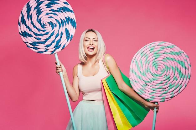 거대한 달콤한 막대 사탕으로 서있는 상단과 치마를 입고 금발 머리를 가진 아름다운 어린 소녀