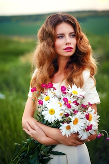 Beautiful young girl with a bouquet of white chamomile flowers