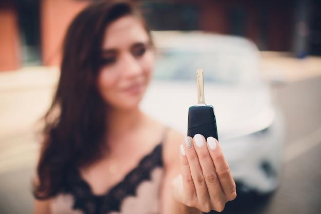 手に車のキーを持つ美しい少女。