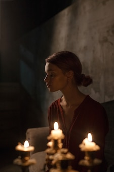 Beautiful young girl with closed eyes in red shirt sitting in gloomy dark room in front of candles in candelabrum