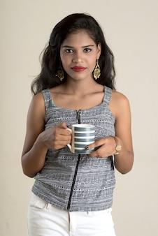 Красивая молодая девушка с чашкой чая или кофе позирует