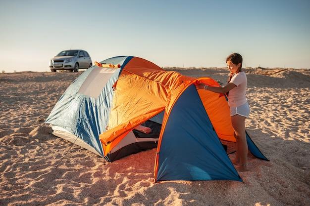 Красивая молодая девушка с темными волосами устанавливает палатку на пляже