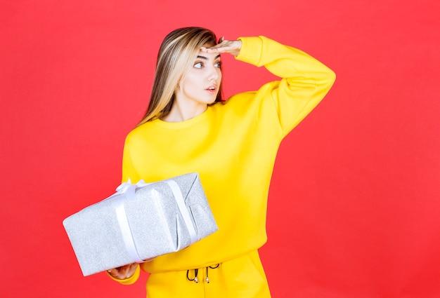 Bella ragazza con scatola regalo guardando il suo fianco sul muro rosso