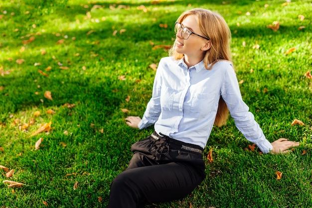 笑顔で緑の芝生に座って熱を楽しんでいるメガネの美しい少女