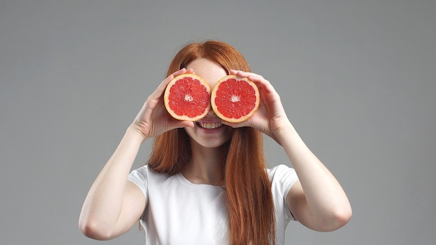Beautiful young girl with grapefruit slices in front of her eyes.