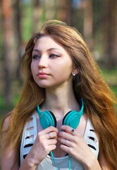 공원에서 헤드폰을 끼고 있는 아름다운 소녀