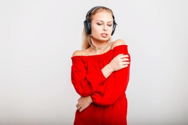 Красивая молодая девушка с наушниками в красном платье, слушая музыку на сером. женский диджей