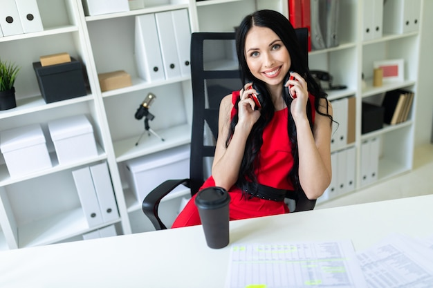 Beautiful young girl with headphones on neck sitting in office at table.