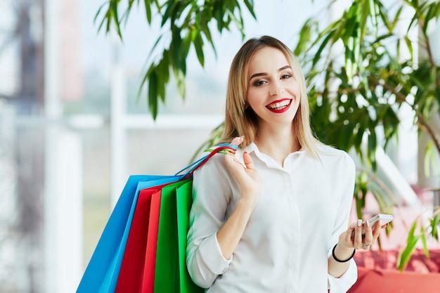 白いブラウスを着て、カラフルな買い物袋を持って立って、携帯電話を持って、ショッピングのコンセプトを明るい茶色の髪と赤い唇を持つ美しい少女。
